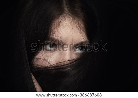 girl covering her face with long black hair