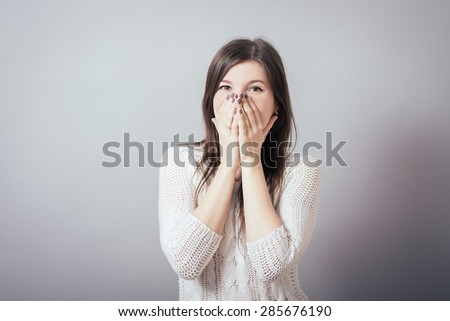girl covering her mouth with her hands - stock photo