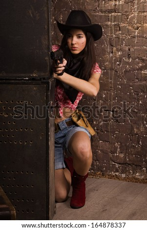 Girl cowboy shoots from a revolver
