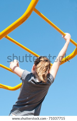 girl crossing elevated monkey bars - stock photo