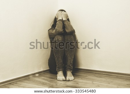 Girl crying in corner and feeling lonely - stock photo
