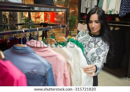 girl customer choosing shirt in clothing store - stock photo
