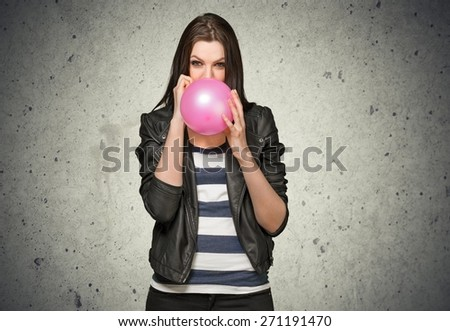 Girl. Cute attractive Caucasian teenage hipster girl blowing a red balloon wearing leather jacket and beanie hat. - stock photo