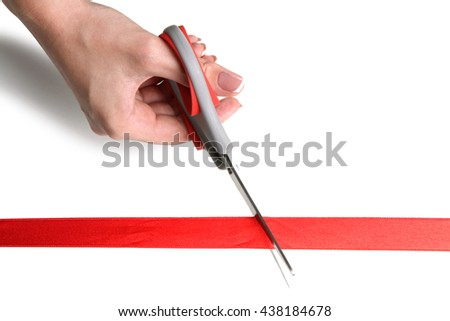 girl cuts red ribbon with scissors isolated on white background - stock photo