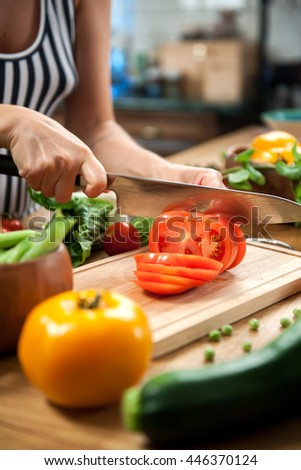 girl cuts ??tomatoes for a salad on the board on a wooden table , surrounded by fresh vegetables , zucchini , green beans , cucumbers ,
