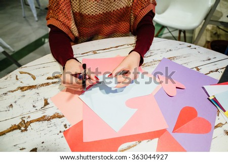 girl cutting out paper heart