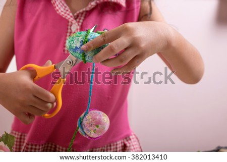 Girl cutting thread with scissors for decorate her easter eggs