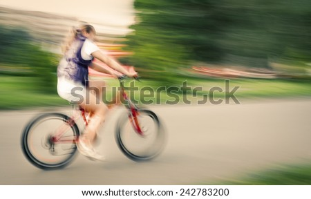 Girl cyclist in traffic on the city roadway. Intentional motion blur and color shift - stock photo