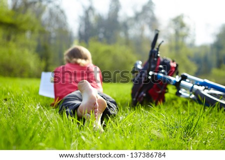 Girl cyclist on a halt reads on green grass outdoors in spring park. Enjoying relaxation - stock photo
