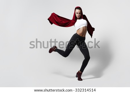 Girl dancer in a studio on a white background in a red robe
