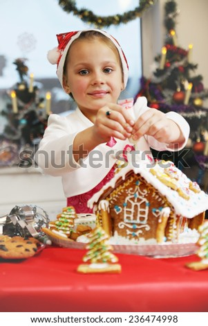 Girl decorates gingerbread house icing from a tube - stock photo