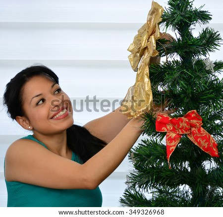 Girl decorating a Christmas tree with baubles - stock photo