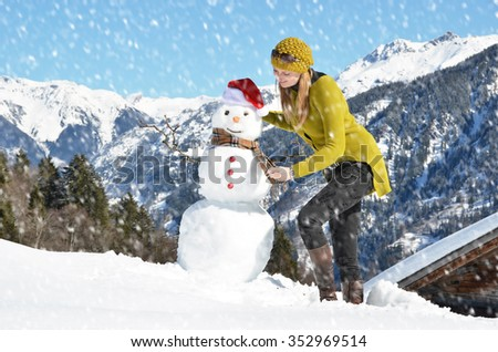 Girl decorating a snowman - stock photo