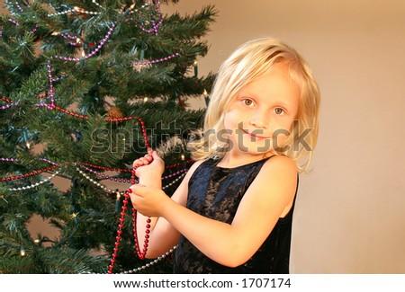 Girl decorating christmas tree - stock photo