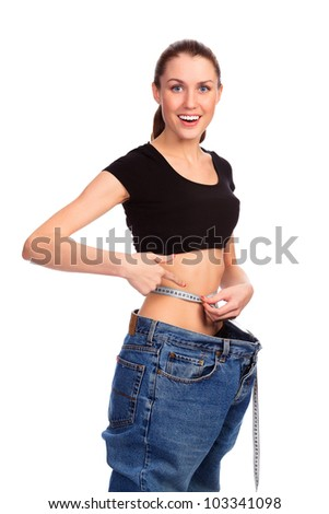 Girl demonstrating weight loss by wearing an old pair of jeans. Isolated on white background - stock photo