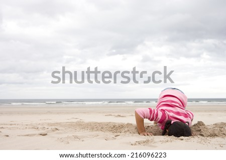 Girl (5-7) digging hole on beach