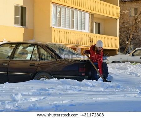 Girl digs car from snowdrift  - stock photo