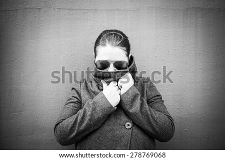 Girl disguised with sunglasses and trenchcoat - stock photo