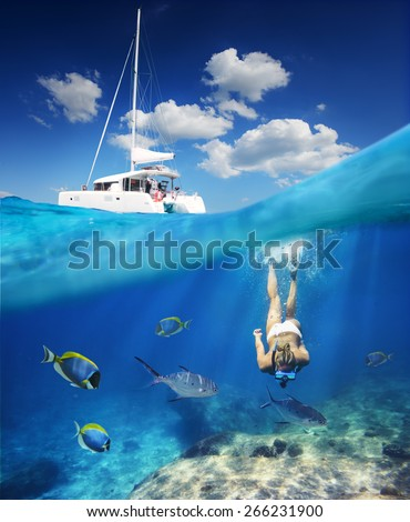 Girl diving in ocean with fishes next to catamaran at sunny day. - stock photo