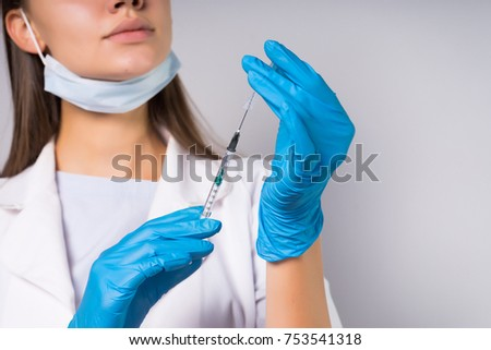 Woman in black dress with syringe with needle