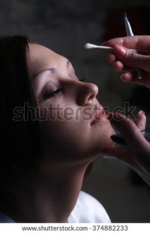 Girl does a make up.Isolated studio portrait
