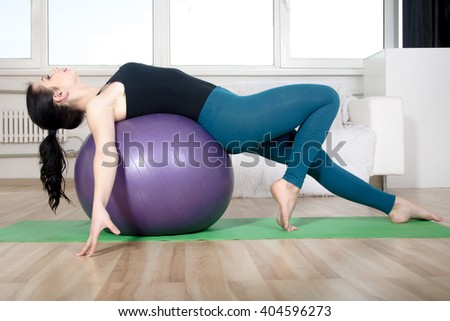 Girl does exercises on a gym ball. She is dressed in sportswear. Concept: fitness, aerobics, health, lifestyle.