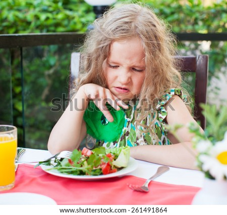 Girl does not like the food. Child with disgust looking at vegetable salad - stock photo