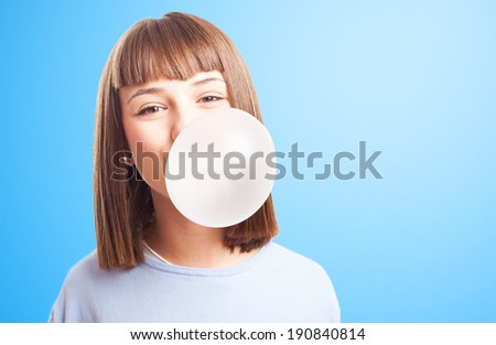 girl doing a bubble with a chewing gum on a white background - stock photo