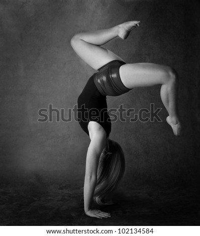 Girl doing back bend in black and white - stock photo
