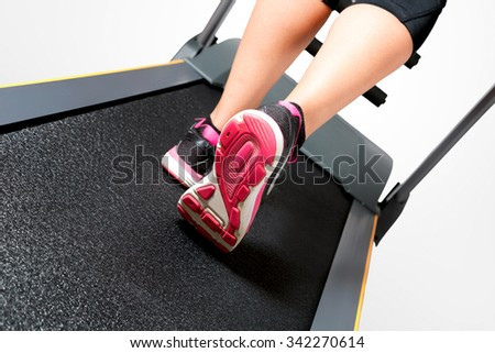 Girl doing cardio training on treadmill on pink black sport shoes - stock photo