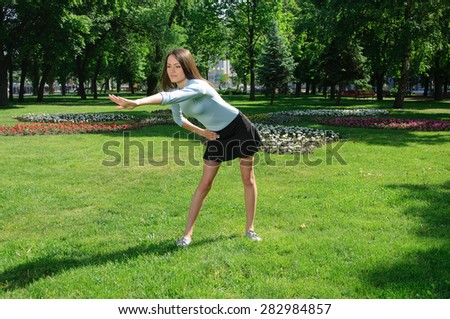Girl doing exercise for the back outdoors at park