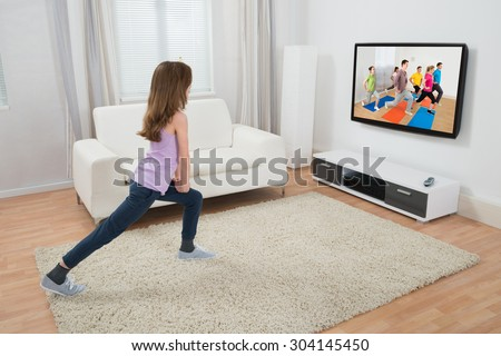 Girl Doing Exercise While Watching Program On Television At Home - stock photo