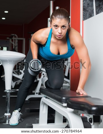 girl doing exercise with dumbbells in fitness room. Attractive fitness woman, trained female body, lifestyle portrait, caucasian model. Fitness theme.  - stock photo