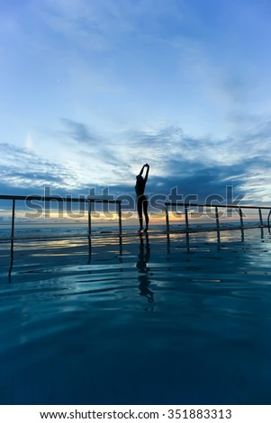 Girl doing gymnastics at the pool at sunset