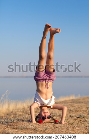 girl doing head stand on the beach - stock photo