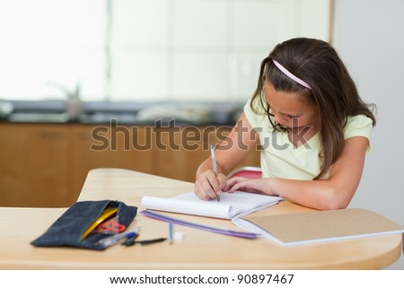 girl doing her homework in the kitchen - stock photo