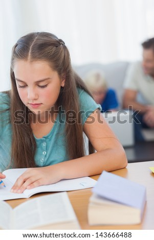 Girl doing her homework with her family behind her