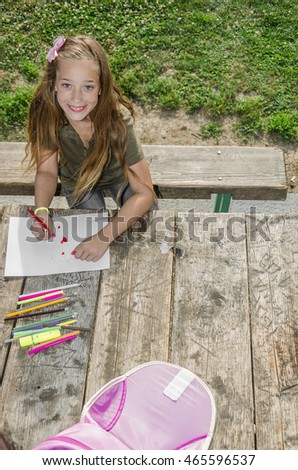Girl doing homework in the park or a line from a height or above