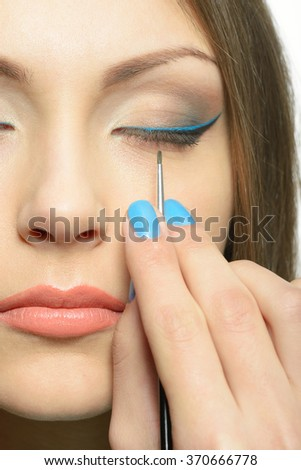 Girl doing makeup. In her hands she holds a paintbrush. She paints her eyes. The girl has brown eyes and she brbnetka. Portrait on a white background in high key