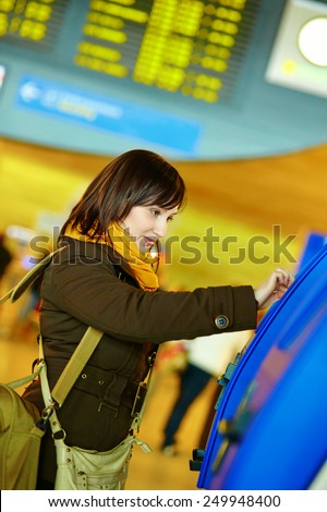 Girl doing self-checkin in the airport before taking her flight - stock photo
