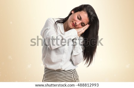 Girl doing sleep gesture over ocher background