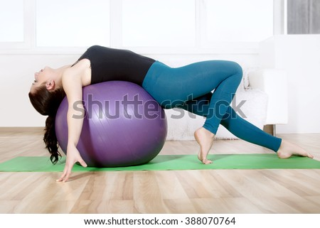 Girl doing stretching her body while lying on gym ball. Concept: lifestyle, fitness, aerobics and health.