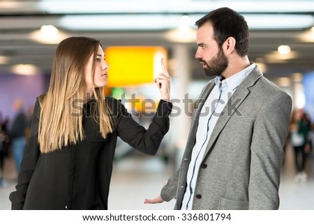 Girl doing the horn sign at her boyfriend over unfocused background