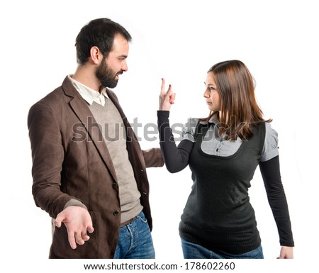 Girl doing the horn sign at her boyfriend over white background