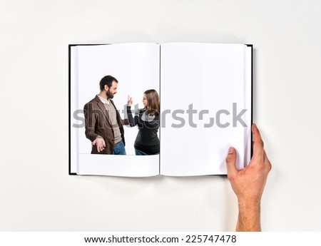 Girl doing the horn sign at her boyfriend  printed on book
