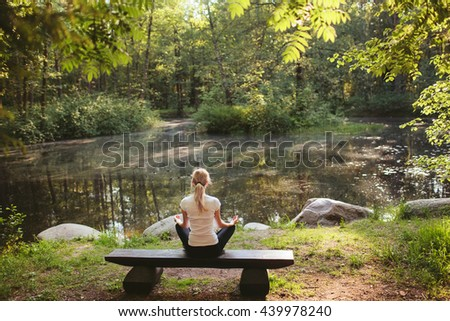 Girl doing yoga in forest lake