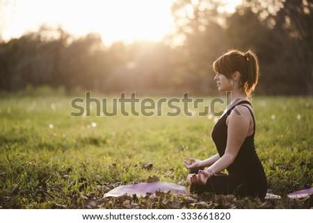 girl doing yoga in park on autumn day - stock photo