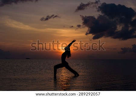 Girl doing yoga in the sea at sunset