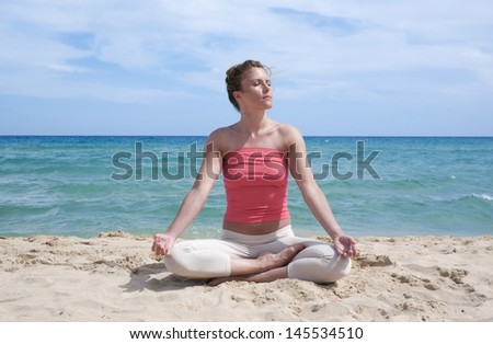 Girl doing yoga meditation on a beach in Sardinia