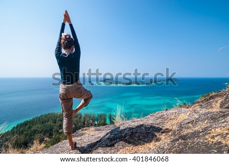 Girl doing yoga on the hill. Ocean in background - stock photo